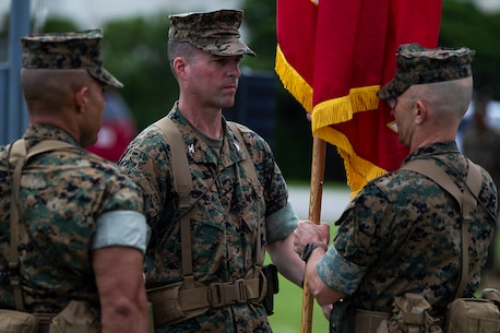 Colonel Robert Brodie, newly appointed commander of the 31st Marine Expeditionary Unit, accepts the unit guidon from Col. Tye R. Wallace during a change of command ceremony at Camp Hansen, Okinawa, Japan, June 13, 2018.