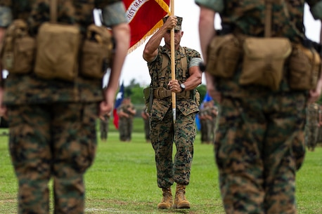 Sergeant Maj. Edwin Mota, sergeant major of the 31st Marine Expeditionary Unit, carries the unit guidon to Col. Tye R. Wallace during a change of command ceremony at Camp Hansen, Okinawa, Japan, June 13, 2018.