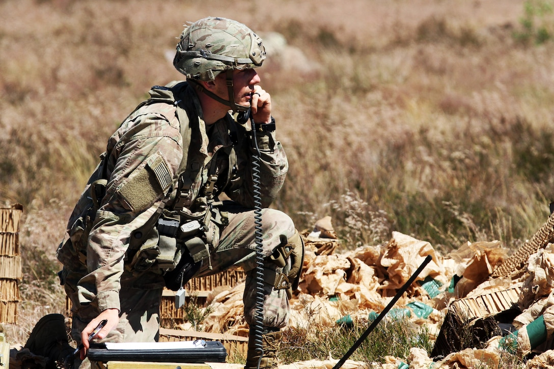 A soldier relays information to his fellow soldiers during a training event.