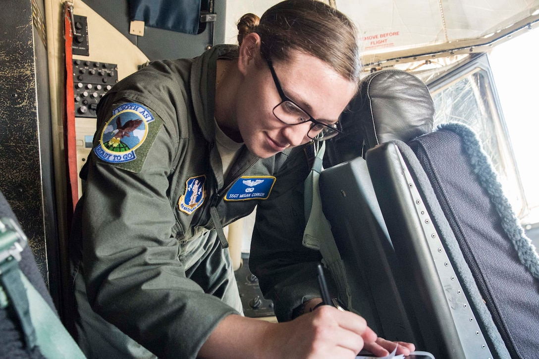 An airman checks data in an airplane's cockpit.