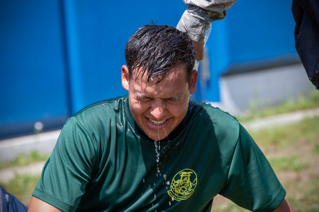 An airman is drenched with cold water after he finishes a four-person relay race.