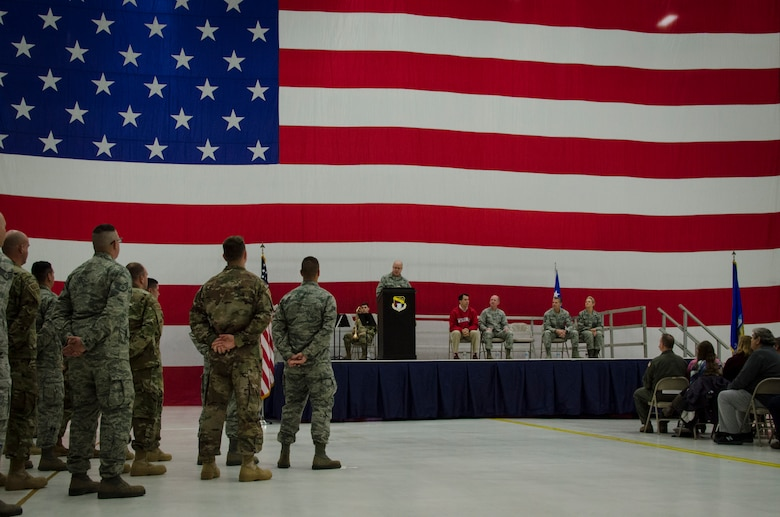 U.S. Air Force Col. James Locke, wing commander of the 128th Air Refueling Wing, speaks to a hangar full of Airmen and their families at a send-off ceremony for deploying Airmen at General Mitchell Airfield in Milwaukee, Wisconsin, Dec. 2, 2017.