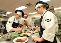 Teammates Airman 1st Class Aubry Burkhardt, Airman 1st Class Madison Farley and Airman Aminah Griffin, 55th Force Support Squadron Sustainment Flight food service apprentices, compete in a top chef competition May 31, 2018 at Offutt Air Force Base, Nebraska. Burkhardt, Farley and Griffin, won the competition and earned a traveling trophy and a day off from work. (U.S. Air Force photo by Charles J. Haymond)