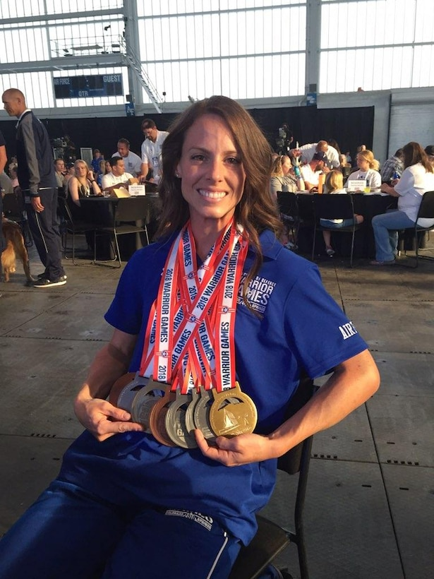 Smiling woman proudly displays gold, silver, and bronze medals around neck