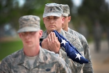 Holding the U.S. flag close, 1st Lt. Michael Jones, crew commander with the 4th Space Operations Squadron, carries the flag during the base retreat ceremony at Schriever Air Force Base, Colorado, June 5, 2018. The ceremony honored the flag and signaled the end of the official duty day. (U.S. Air Force Photo by Dennis Rogers)