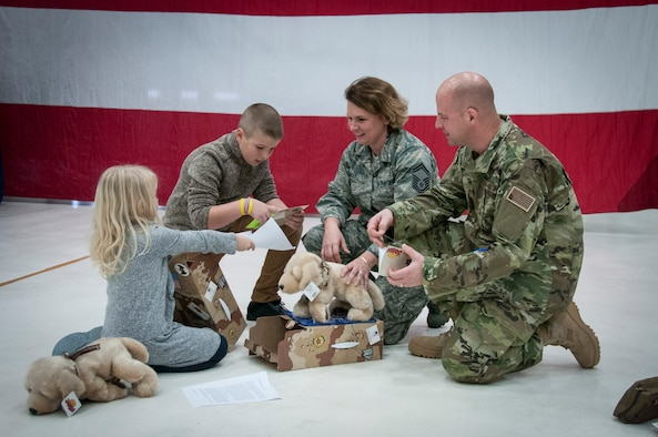 U.S. Air Force Senior Master Sgt. Kristen Stanley and her family open gifts from the USO of Wisconsin after a sendoff ceremony at General Mitchell Air Field in Milwaukee Dec. 2, 2017.