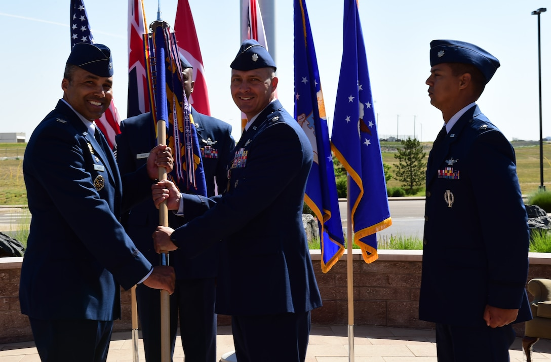 Lt. Col. Ethan Mattox, center, 11th Space Warning Squadron outgoing commander, relinquishes the guidon to Col. Lorenzo Bradley, left, 460th Operation Group commander, June 12, 2018, on Buckley Air Force Base, Colorado. The 11 SWS supports the base mission of space-based missile warning alongside the 2nd and 8th Space Warning Squadrons. (U.S. Air Force photo by Senior Airman AJ Duprey)