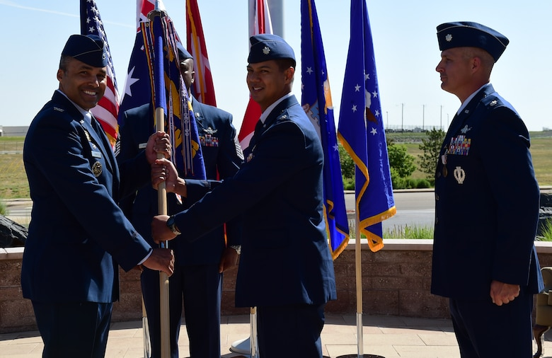 Lt. Col. Michael Kruk, center, 11th Space Warning Squadron incoming commander, receives the guidon, symbolizing the official change of command, June 12, 2018, on Buckley Air Force Base, Colorado. The 11 SWS supports the base mission of space-based missile warning alongside the 2nd and 8th Space Warning Squadrons. (U.S. Air Force photo by Senior Airman AJ Duprey)