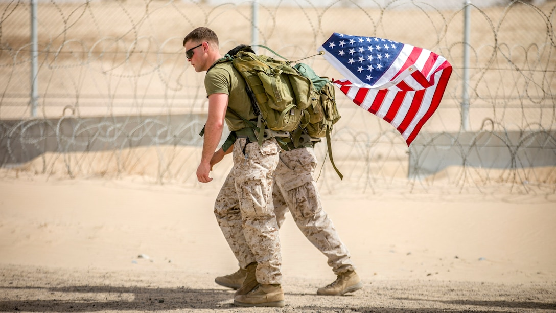 Two Marines carry an American flag as they hike by a barbed wire fence in desert terrain.