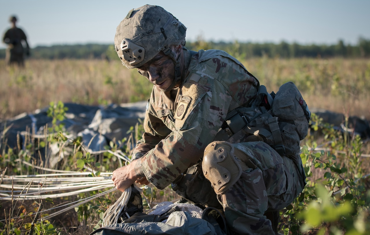 Army Spc. Sean Shelts, with the 1st Battalion, 508th Infantry Regiment, packs his parachute and collects his gear after jumping from an aircraft near Rukla, Lithuania, as part of exercise Swift Response 18, June 9, 2018. Army photo by Spc. Andrew McNeil