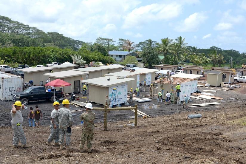 Service members walk near under construction shelters.