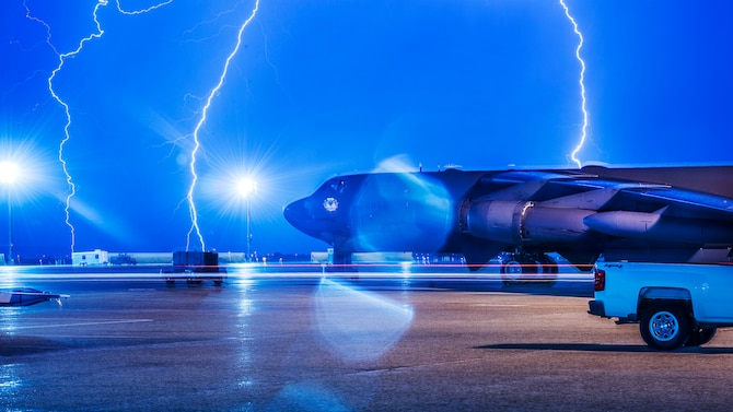 Lightning strikes behind B-52H Stratofortress at Minot Air Force Base, N.D., Aug. 8, 2017. . During lightning storms, personnel are reminded to stay sheltered in buildings, underground shelters or automobiles.