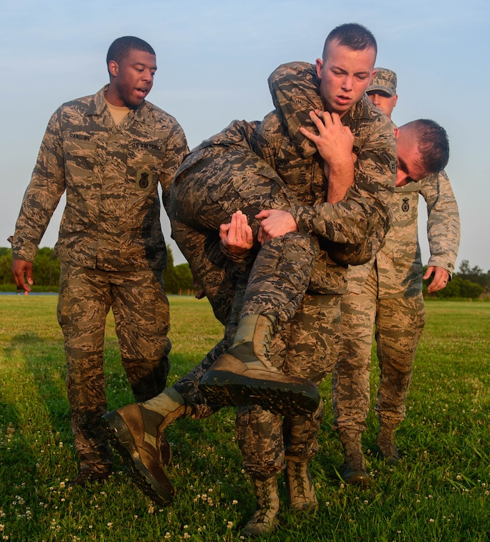 U.S. Air Force Airman 1st Class Nicholas Smoak, 633rd Security Forces Squadron entry controller, fireman carries another candidate during an emergency services team tryouts at Joint Base Langley-Eustis, Virginia, June 8, 2018. During the fitness obstacle course, the five first responders performed a low crawl, high crawl, ammunition can carry and a fireman carry. (U.S. Air Force photo by Senior Airman Derek Seifert)