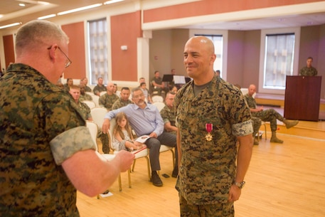 U.S. Marine Corps Col. David S. Owen (left) awards the Legion of Merit to Sgt. Maj. Rene Salinas, (right) former sergeant major of II Marine Expeditionary Force Information Group (MIG), during a relief and appointment ceremony at Camp Lejeune, N.C., June 8, 2018. After 30 years of service, Salinas retired and relinquished his duties of II MIG sergeant major to Sgt. Maj. Joy M. Kitashima. (U.S. Marine Corps photo by Lance Cpl. Tanner Seims)