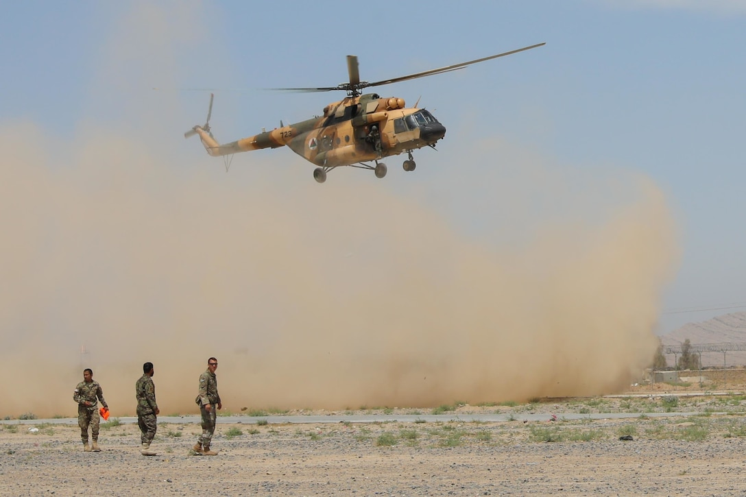 Army Sgt. Christian Ladd, a combat medic assigned to 2nd Battalion, 1st Security Force Assistance Brigade, and two Afghan soldiers wait for an Mi-17 helicopter to land, May 8, 2018, during a medical evacuation exercise hosted by soldiers from the 2nd Battalion, 1st Security Forces Assistance Brigade at Regional Military Training Center-Kandahar in Kandahar, Afghanistan. Army photo by Staff Sgt. Neysa Canfield