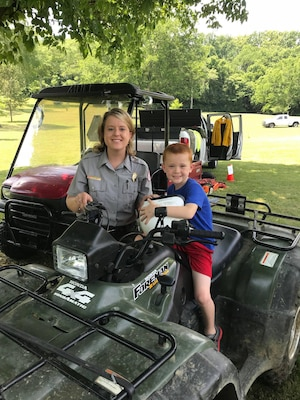 "Park Ranger Ashley Webster shows a young boy the all-terrain vehicles the Corps of Engineers use when doing trail work during the ""Touch a Truck"" event June 9, 2018 at Cordell Hull Lake in Carthage, Tenn. (Courtesy Asset)"
