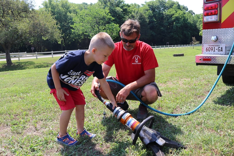 """A member of the Smith County Rescue Squad Extrication team shows off the """"jaws of life"""" to a youngster during the """"Touch a Truck"""" event June 9, 2018 at Cordell Hull Lake in Carthage, Tenn. (USACE Photo by Ashley Webster)"""