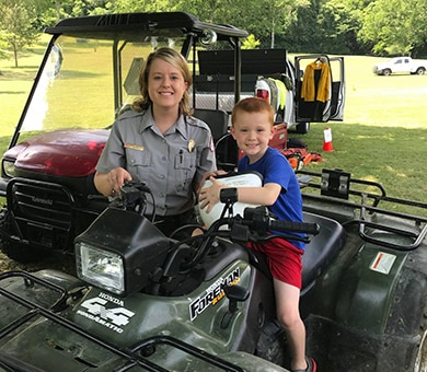 """Park Ranger Ashley Webster shows a young boy the all-terrain vehicles the Corps of Engineers use when doing trail work during the """"Touch a Truck"""" event June 9, 2018 at Cordell Hull Lake in Carthage, Tenn. (Courtesy Asset)"""