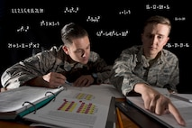 Staff Sgt. Lee Rimell, noncommissioned officer in charge of financial management operations, and Senior Airman Nathan Saelens, financial management technician, both with the 50th Comptroller Squadron, discuss homework assignments in a classroom at Schriever Air Force Base, Colorado, June 12, 2018. Rimell and Saelens have successfully completed the Math Concepts course offered through Colorado Christian University via Schriever AFB's Professional Development Center. The next session of the course begins July 24. (U.S. Air Force photo illustration by Staff Sgt. Matthew Coleman-Foster)