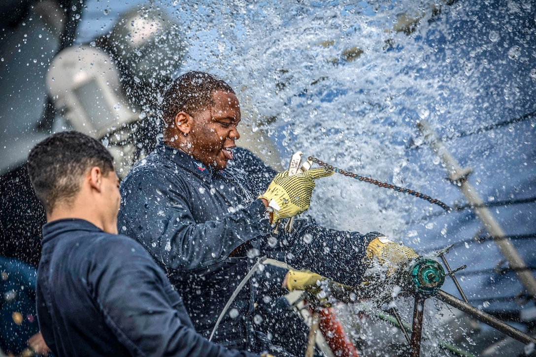 Water spews from a ruptured pipe a sailor is trying to fix, as another looks on.