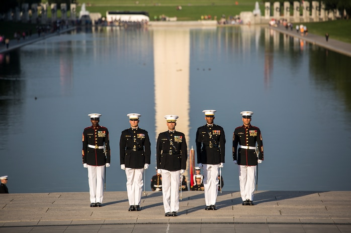 Marines with the Marine Barracks Washington D.C. parade marching staff stand at attention during the Sunset Parade at the Lincoln Memorial, Washington D.C., June 12, 2018.