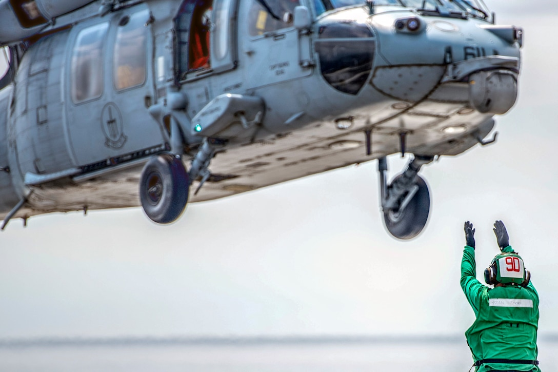 A sailor in green holds his arms up as a helicopter launches above him
