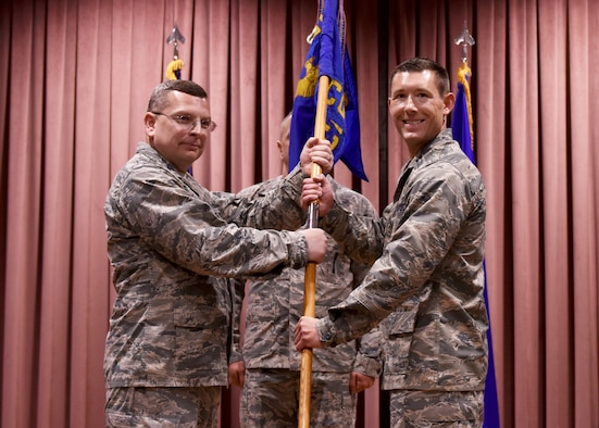 U.S. Air Force Col. David Williams, 39th Mission Support Group commander, passes the guidon to Capt. Joseph Misch as he assumes command of the 39th Contracting Squadron during a change of command ceremony at Incirlik Air Base, Turkey, June 13, 2018.
