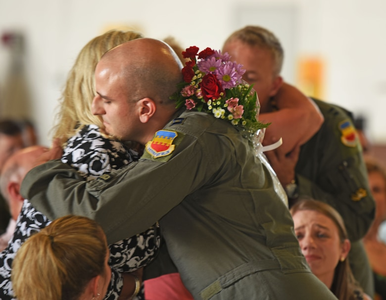 U.S. Air Force Captains John Nygard and Salvador Cruz, 79th Fighter Squadron instructor pilots, present flowers to friends and family members during a Distinguished Flying Cross presentation (DFC) ceremony at Shaw Air Force Base, S.C., June 7, 2018.