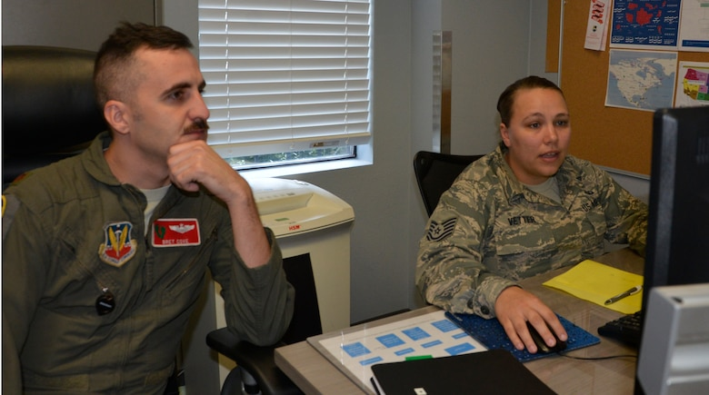 Maj. Bret Cove, Air Force Rescue Coordination Center Assistant Director of Operations, listens as Tech. Sgt. Brittany Vetter, AFRCC Operations Flight NCO in Charge, reviews the day's notifications during a shift change in the AFRCC operations room. (Photo by Mary McHale)
