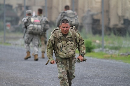 Sgt. 1st Class Fabian Balarezo, an Army Reserve Soldier assigned to the Regional Training Site – Maintenance Fort Hood, maintains a steady pace as he wears a 33 lbs ruck suck during the German Armed Forces Proficiency Badge 12-kilometer ruck march. Balarezo was one of more than 75 Soldiers and Airmen who strived to earn the badge for military proficiency. (U.S. Army Reserve photo by Sgt. 1st Class Emily Anderson, 80th Training Command)