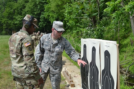 Air Force Cadet Patrick Forbus pinpoints the area on the pistol target that he successfully shot during the German Armed Forces Proficiency Badge pistol markmanship test. Forbus was one of more than 75 Soldiers and Airmen who strived to earn the badge for military proficiency. (U.S. Army Reserve photo by Sgt. 1st Class Emily Anderson, 80th Training Command)