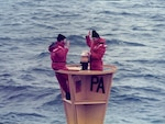 "Then Coast Guard Chief Petty Officer Bob Trainor reenlists on ""PA"" Lighted Buoy in the Straits of Juan de Fuca near the state of Washington while stationed aboard Coast Guard Cutter Fir, Feb. 5, 1986."