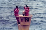 """Then Coast Guard Chief Petty Officer Bob Trainor reenlists on """"PA"""" Lighted Buoy in the Straits of Juan de Fuca near the state of Washington while stationed aboard Coast Guard Cutter Fir, Feb. 5, 1986."""