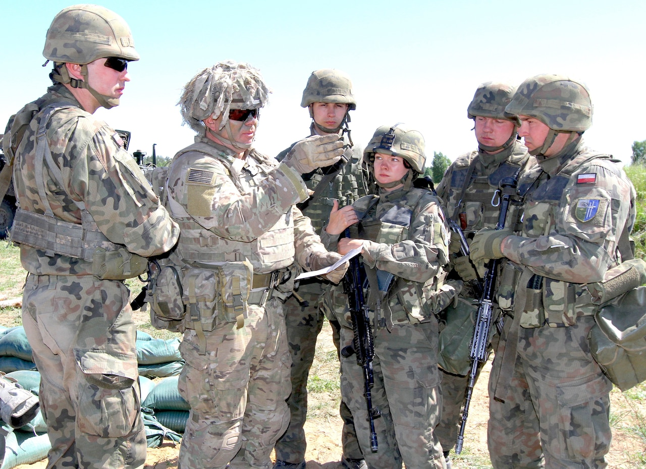 Army Staff Sgt. Marion Szwcyk, weapons squad leader from Apache Troop, 1st Squadron, 2nd Cavalry Regiment, Battle Group Poland, briefs Polish soldiers from the 15th Mechanized Brigade on range cards during Exercise Saber Strike 18 in Wyreby, Poland.