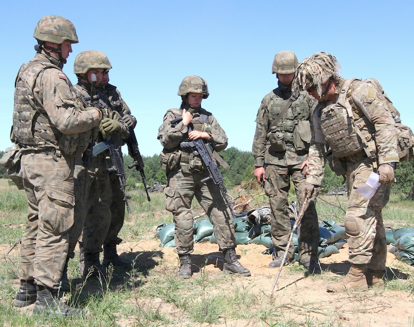 Army Staff Sgt. Marion Szwcyk, weapons squad leader from Apache Troop, 1st Squadron, 2nd Cavalry Regiment, Battle Group Poland, instructs Polish soldiers from the 15th Mechanized Brigade on space needed to dig fighting positions during Exercise Saber Strike 18 in Wyreby, Poland.
