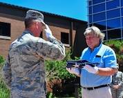 Reserve Citizen Airman Maj. Scott D. Allen, 910th Airlift Wing chief of Public Affairs, salutes a 48-star flag after presenting it to Charles Robert Johnson Jr. in front of the YARS headquarters building, June 14, 2018.