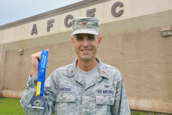 Man wearing Air Force uniform stands and smiles at center holding Boston Marathon completion medal.