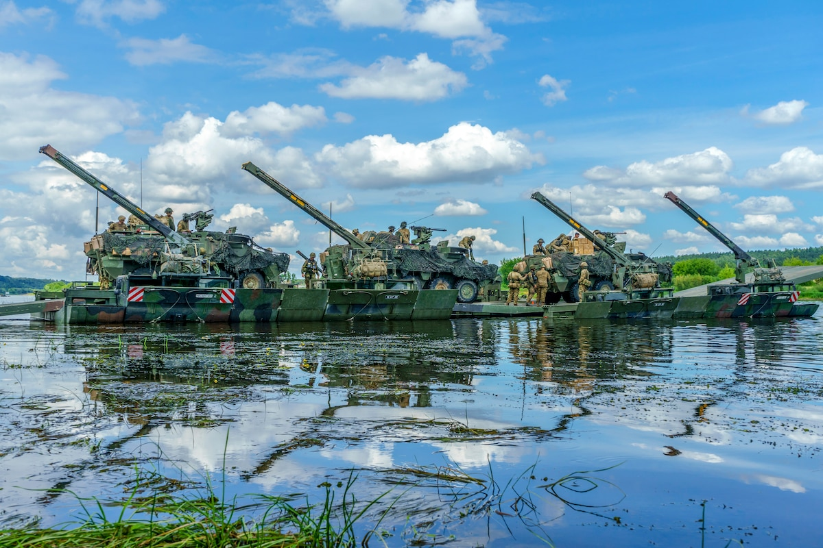 Tanks and service members cross a river on an amphibious platform.