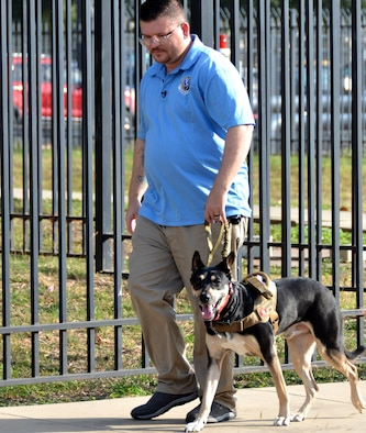 Ryan Kaono, a support agreement manager with the Air Force Installation and Mission Support Center, takes his service dog Romeo for a walk around his work center. Thanks to Romeo, Kaono is able to quickly transition through bouts of anxiety and night terrors. (U.S. Air Force photo by Armando Perez)