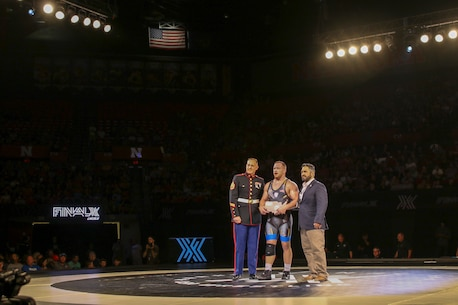 Staff Sgt. Craig Soltys, the staff noncommissioned officer-in-charge of Recruiting Substation Lincoln, presents a plaque to Kyle Snyder, Columbus, Ohio native, Olympic Gold Medalist, and world team member, at the FinalX Senior Freestyle World Team Trials at Bob Devaney Sports Center in Lincoln, Neb. June 9, 2018.