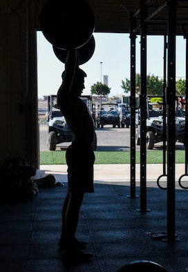 A pararescueman from the 48th Rescue Squadron performs an overhead press at Davis-Monthan Air Force Base, Ariz., June 6, 2018. 48th RQS pararescuemen constantly exercise and monitor their mental and physical health in order to tackle injuries and physical discomforts proactively to maintain deployment readiness status through the Human Performance Optimization program. (U.S. Air Force photo by Airman 1st Class Frankie D. Moore)