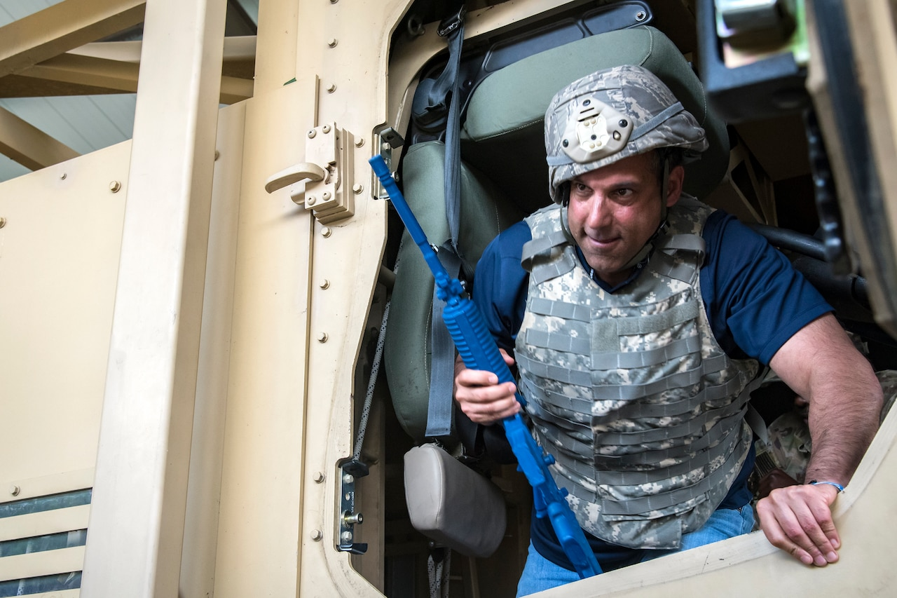 Michael Cherenson, Joint Civil Orientation Course (JCOC) 88 member, climbs out of a mine-resistant, ambush-protected vehicle roll-over simulator, June 13, 2018, at Moody Air Force Base, Ga. The mission of JCOC is to increase the public's understanding of the military through engagements between the armed forces and course members. (U.S. Air Force photo by Airman 1st Class Eugene Oliver)