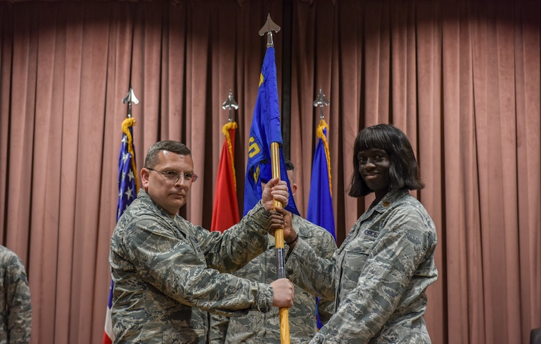 Col. David Williams, passes the guidon to Maj. Francine Kwarteng as she assumes command of the 39th Logistics Readiness Squadron.
