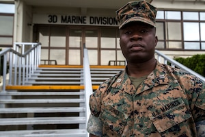 A Marine poses for a photo outside the 3rd Marine Division headquarters building.