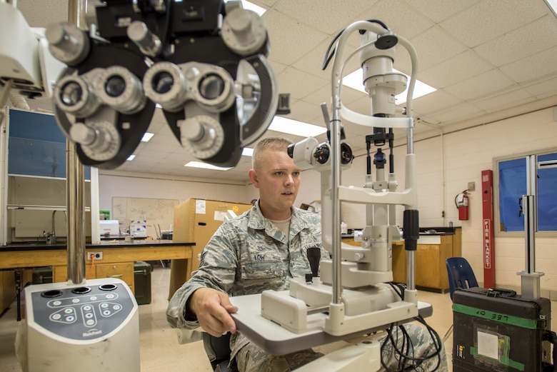 U.S. Air Force Tech. Sgt. Eric Low, a medical technician from the New Hampshire Air National Guard's 157th Air Refueling Wing, inspects optometry equipment for a health-care clinic at Lee County High School in Beattyville, Ky., June 14, 2018. The clinic is one of four being staffed by military health-care professionals in Eastern Kentucky from June 15 to June 24 as part of an Innovative Readiness Training mission called Operation Bobcat. The mission provides military forces with crucial expeditionary training while offering no-cost medical, dental and optometry care to area residents. (U.S. Air National Guard photo by Lt. Col. Dale Greer)