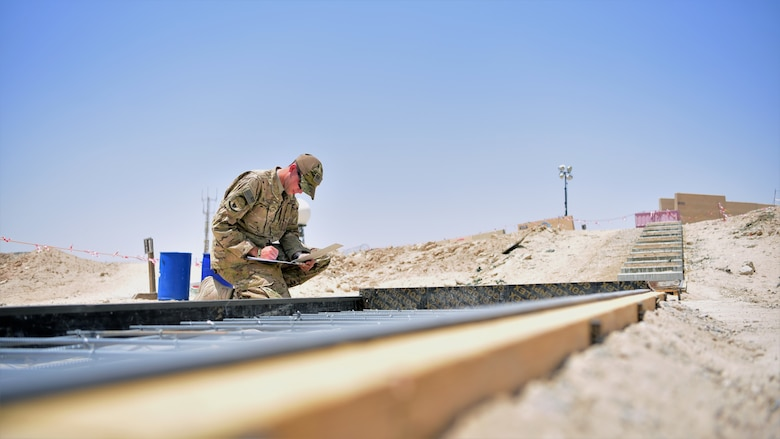 Staff Sgt. Kevin Welch, 386th Expeditionary Civil Engineer Squadron project manager, inspects the rebar reinforcement for a sidewalk construction project, June 15, 2018, at an undisclosed location in Southwest Asia. His father, Chief Master Sgt. Chad Welch, 386th Air Expeditionary Wing command chief, is now deployed to the same location.