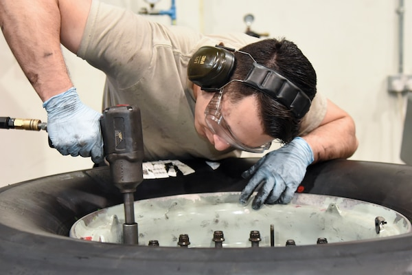 Airman 1st Class Christian Risenhoover, 379th Expeditionary Maintenance Squadron wheel and tire technician, removes bolts from a C-17 Globemaster III wheel assembly at Al Udeid Air Base, Qatar, June 13, 2018. The 379 EMXS supplies an average of 180 wheels a month to various deployed aircraft. (U.S. Air Force photo by Staff Sgt. Enjoli Saunders)
