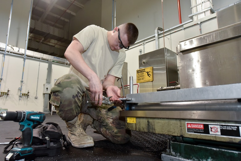 Senior Airman Justin Travis, 379th Expeditionary Maintenance Squadron metals technician, installs a bump stop on a washer grate at Al Udeid Air Base, Qatar, June 13, 2018. The bump stop serves as a mechanism to prevent the grate from extending past a certain point when servicing aircraft wheels. (U.S. Air Force photo by Staff Sgt. Enjoli Saunders)