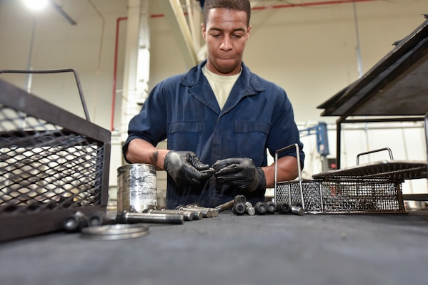 Senior Airman Jahlil Moses, 379th Expeditionary Maintenance Squadron wheel and tire technician, inspects bolts from a C-17 Globemaster III wheel assembly at Al Udeid Air Base, Qatar, June 13, 2018. The 379 EMXS supplies an average of 180 wheels a month to various deployed aircraft. (U.S. Air Force photo by Staff Sgt. Enjoli Saunders)