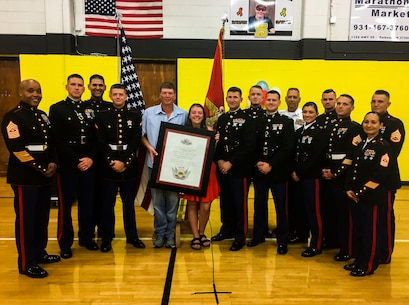 """Left to right, Sgt. Maj. Cortez L. Brown, Maj. Jonathan W. Landers, Gunnery Sgt. Isaac M. Ishak, Pfc. Gavin G. Northcutt, Marty Northcutt, Tori Northcutt, Col. Jeffrey C. Smitherman, Staff Sgt. Brian D. Raney, Capt. Kyle R. Kuhn, retired Master Sgt. Bud Schell, Capt. Asia Pastor, Gunnery Sgt. Nathan D. Mitchaner, Staff Sgt. Jon P. Slayton, Sgt. Maj. Rena M. Bruno and Staff Sgt. James B. Benham stand with Hunter A. Northcutt's Honorary Marine award at Pelham Elementary School, Pelham, Tennessee, June 13, 2018. Only the Commandant of the Marine Corps can officially designate an individual as an """"Honorary Marine"""" to acknowledge extraordinary contributions to the Marine Corps. (U.S. Marine Corps photo by Sgt. Mandaline Castillo)"""